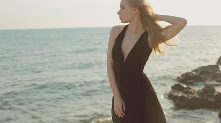 giydirmek : Thoughtful woman with long hair wearing a long black dress standing on a rock by the sea at sunset and thinking