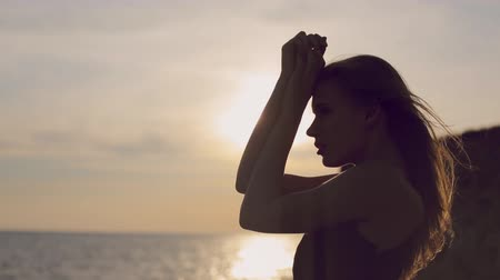 tmavé vlasy : Full of thoughts woman with flowing hair wearing a dress standing by the sea at sunset on the rocky shore Dostupné videozáznamy