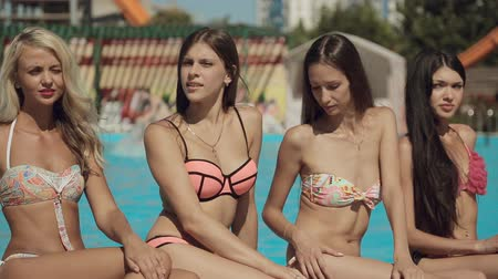 jovens : Sexy models wearing bikini sitting by the pool in the summer