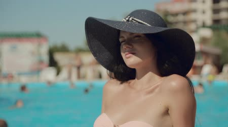 шляпа : Relaxed girl in a hat and bikini sunbathing on the edge of the pool Стоковые видеозаписи