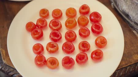repast : Cook prepares cherry tomatoes to stuffing in a restaurant