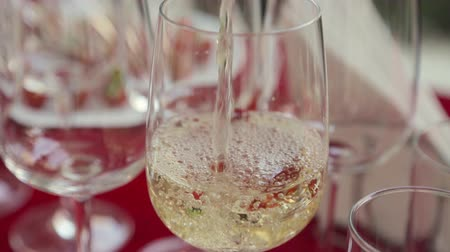 setting : Waiter pours cold white wine in glasses on a banquet