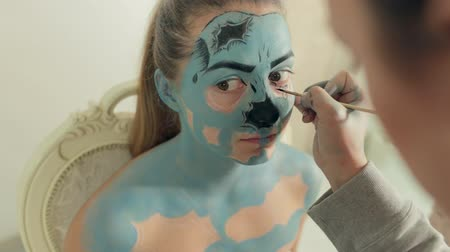 greasepaint : Visagist applies makeup of zombie to girl at Halloween party Stock Footage