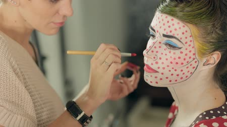 greasepaint : Visagist applies the red dots on the models face, the image of the heroine of the comic book pop art