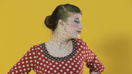 greasepaint : Funny girl made up as comics heroine shows different emotions on a bright yellow background in the studio