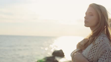posando : Sensual blond girl wearing a cardigan near the sea at sunset Stock Footage