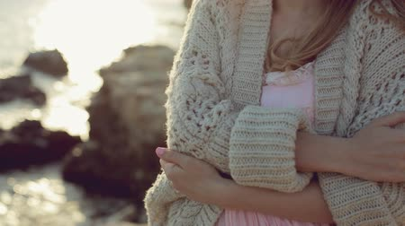 posando : Sensual green-eyed blonde wearing a knitted jacket standing near the sea at sunset