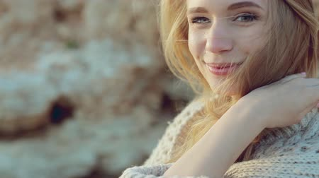 pulóver : Beautiful green-eyed blonde standing near the sea in windy weather