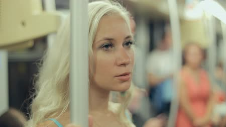 subdivisão : Thoughtful blonde wearing a blue dress standing in a subway car