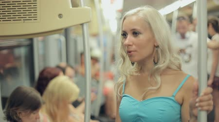 subdivisão : Beautiful blonde reading in a crowded metro car