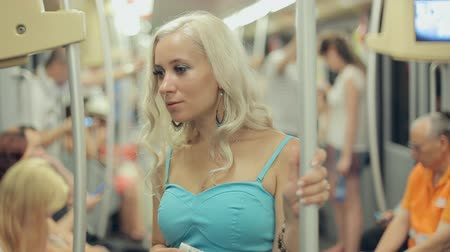 tüp : Beautiful blonde standing in a crowded car of the underground in Milan