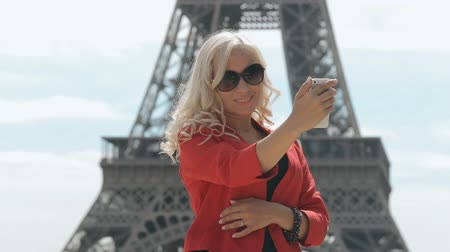 okulary przeciwsłoneczne : Attractive blonde in sunglasses doing selfie against the backdrop of the Eiffel Tower in Paris