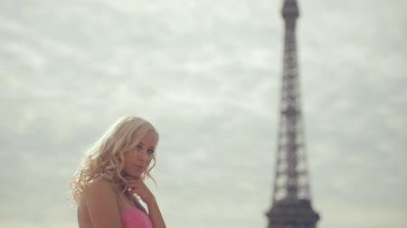 башни : Thoughtful woman dressed in festive pink strapless dress near the Eiffel Tower in Paris Стоковые видеозаписи
