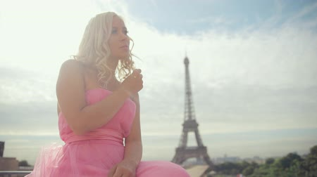 francja : Thoughtful woman dressed in festive pink strapless dress near the Eiffel Tower in Paris Wideo