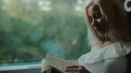 otobüs : Beautiful blonde  reading a book in the train Stok Video