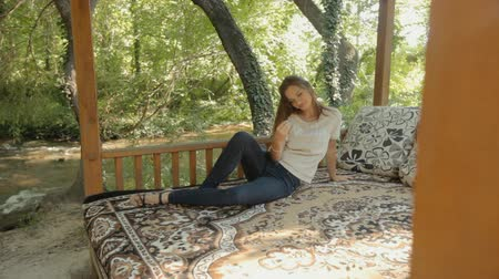 rookery : Young woman lying on a carpet in the gazebo in the woods Stock Footage