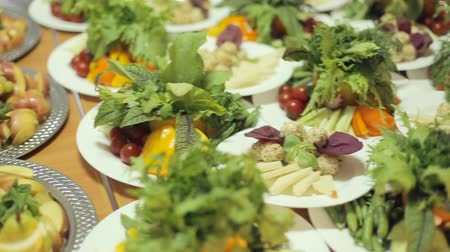 placas : Many different dishes with vegetables, fruits on a large platters on a banquet