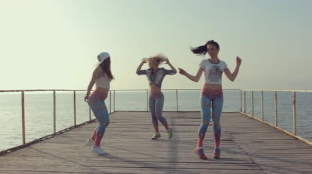 латинский : Twerk by young energetic teen girls on a wooden pier near the sea Стоковые видеозаписи