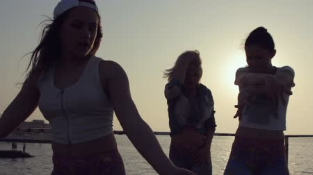 biodro : Three cheerful girls dressed in the same tights dancing at sunset near the sea
