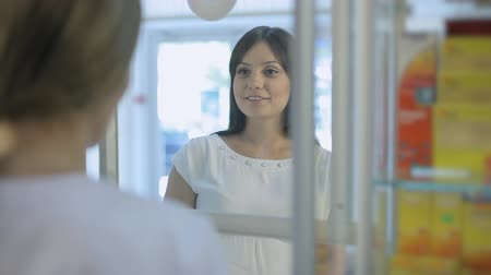 фармацевт : Young pregnant woman talking to pharmacist in a drugstore