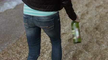 treading : Girl walking on the beach with a bottle of wine in her hands