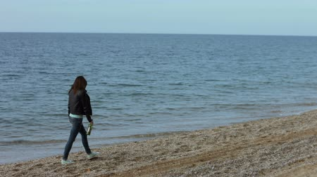 treading : Lonely woman walking on the beach with a bottle of wine