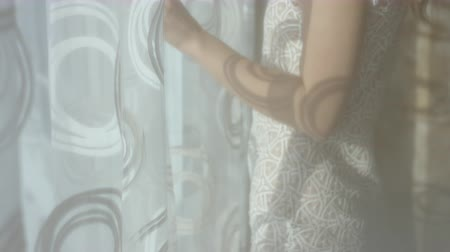 rolety : Charming woman dressed in white elegant dress standing by the window Wideo