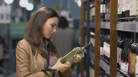 beyaz şarap : Attractive woman chooses the wine bottle at the supermarket