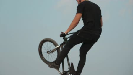 extremo : Young man in black sportswear is doing flips and other complex stunts on the bike during dirt jumping competition.