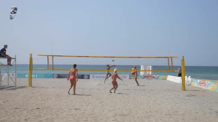 четыре человека : Four sports girls in bathing suits playing volleyball on the beach