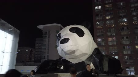 パンダ : Chengdu, Sichuan province, China - Sept 19, 2019 : People taking photo in front of a panda sculpture illuminated at night at International Finance Center IFS