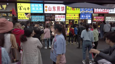 asya mutfağı : Chengdu, Sichuan province, China - Oct 4, 2019 : People standing in line in front of snacks stores during the chinese national holidays golden week. Stok Video