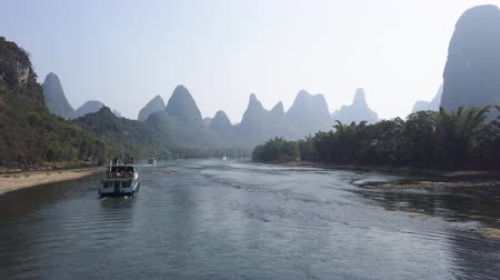 известняк : Boat on Li river cruise and karst formation landscape in the fog between Guiling and Yangshuo, Guangxi province, China