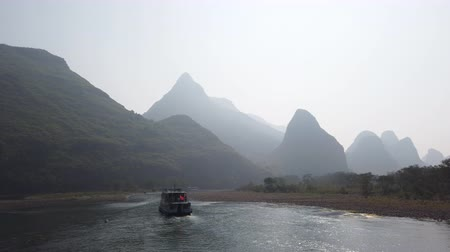 kalker : Boat on Li river cruise and karst formation landscape in the fog between Guiling and Yangshuo, Guangxi province, China