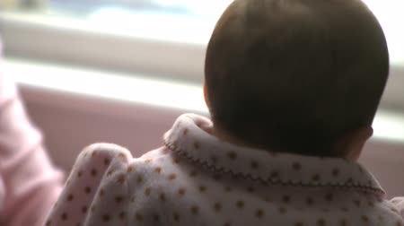 göğüs : A two month old infant looking out a window. Stok Video