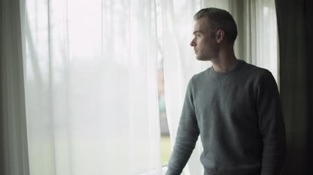 алкоголизм : A depressed man stands at a window on a stormy cold day and looks out the window.