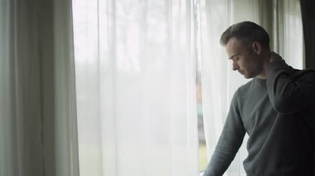 потеря : A depressed man stands at a window on a stormy cold day and looks out the window.