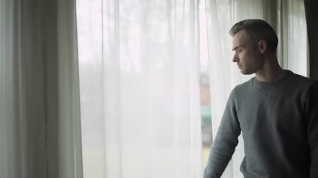matança : A depressed man stands at a window on a stormy cold day and looks out the window.