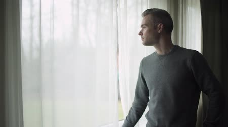 bipolar disorder : A depressed man stands at a window on a stormy cold day and looks out the window.