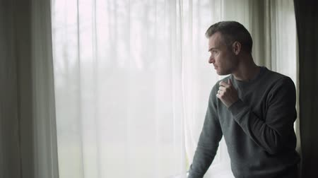 жертва : A depressed man stands at a window on a stormy cold day and looks out the window.