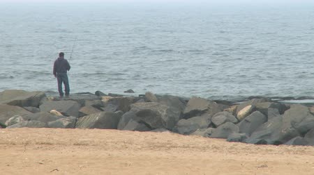 рыболовство : Man using a fishing pole from the shore of New Jersey Стоковые видеозаписи