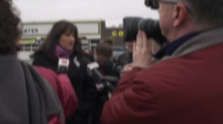 entrevista : Camera crews and reporters interview people about breaking news.