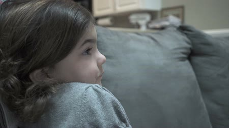 ailelerin : Views of a child engrossed in a visual media entertainment.  The child is alone and staring blankly at the program on the screen. It is possible the child is being influenced in a positive or negative way by what they are watching. Stok Video