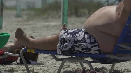 paunchy : An obese man lounging on a beach.