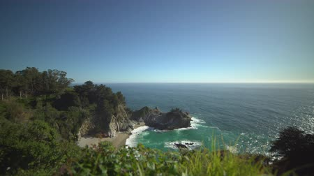 západ : A view of McWay Falls located in Julia Pfeiffer Burns State Park. The waterfall is stunning, dropping some 80 feet onto a pristine beach in an enchanting cove.