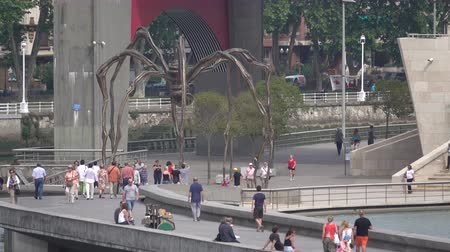 İspanya : A view of people looking at a spider sculpture by Louise Bourgeois around the Guggenheim in Bilbao, Spain