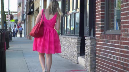 rendes : A view of a woman in a bright pink dress walking down a sidewalk