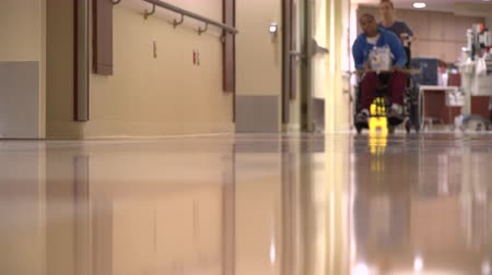 ér : Low angle view of a patient being wheeled down a hall