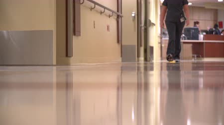 ér : A scene of two nurses walking down the hall in a modern hospital