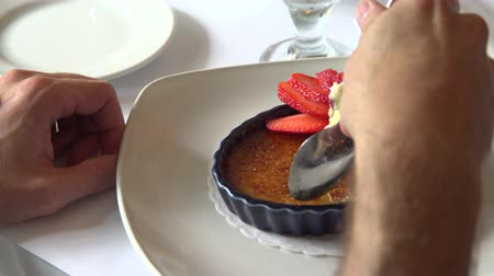 preparado : A person eating a gourmet dessert with a spoon